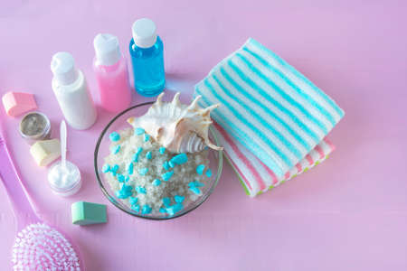 Spa body care concept. Sea salt for exfoliation, cleansers, towels on pink wooden background. Foto de archivo