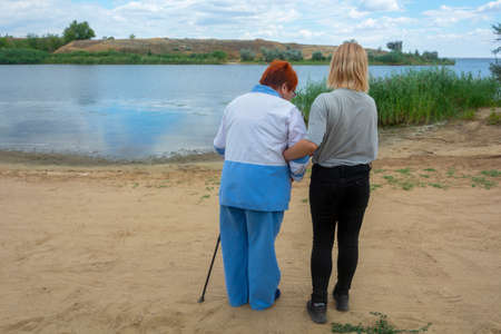Young woman helps her older grandmother to walk. Granddaughter supports grandmother outdoors. Concept of helping older generation, caring for loved ones, family. Soft focus.