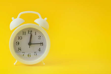 White vintage alarm clock on a bright yellow background. Clock with black arrows. Copy space, banner. Stock Photo