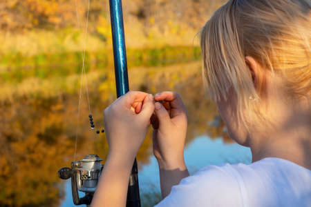 Young woman fisherman catches fish with fishing rod in autumn on the river. Fisherman's day concept. 版權商用圖片