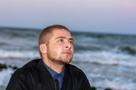 Smiling young Caucasian man with beard on background of the sea and waves with white foam. Selective focus, close-up. 版權商用圖片