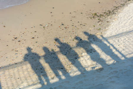 Shadows of people on sand near the sea. Concept of recollection, farewell to loved ones, departure to another reality, death.