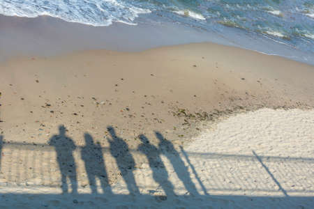 Shadows of group of people on the seashore. Concept of recollection, pandemic, departure to another reality.