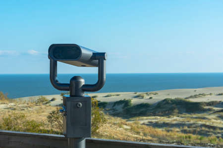 Binoculars in an iron case for sea tourists on the shore. Coin-operated binocular viewer.