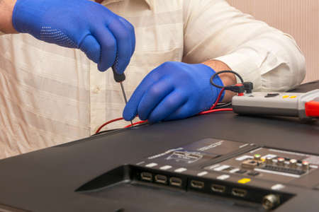 Repair of LCD TV, engineer in gloves with screwdriver removes the back panel of monitor. Selective focus, close-up.