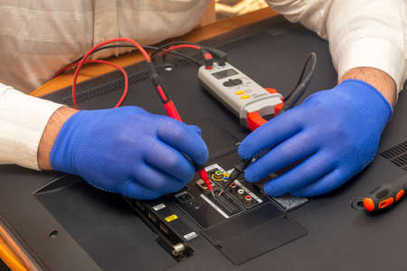 Engineer in service center repairs an LCD TV. Gloved hands measure the resistance on back of the monitor with multimeter. Selective focus, close-up.