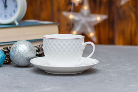 White cup with hot tea or coffee in winter composition. Christmas and New Year concept. Selective focus, fog view.