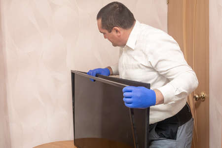 Wizard removes frame of LCD TV. Home monitor repair. Calling an engineer for repair. Selective focus.