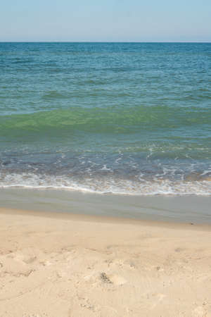 Seashore with soft wave on sandy beach. Natural background for summer vacation.