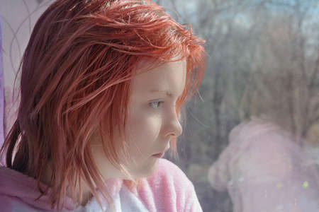 Teenage girl with red hair looks out window to street. Sad emotions on face. Close-up, selective focus.
