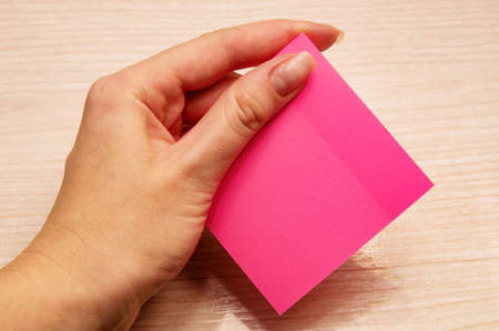 Left female hand holds pink notes for memos