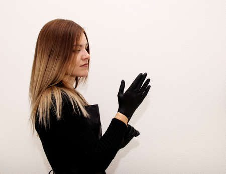 Young fair-haired girl in black stands on a white background and puts on black vinyl disposable gloves