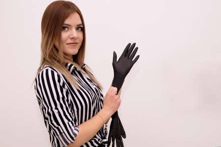Young girl manicurist stands and puts on black gloves Stock Photo