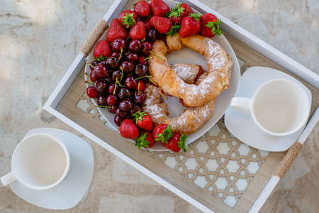 Summer breakfast served on the terrace. Croissants with cherry and strawberry. Healthy breakfast outdoors. High-quality photo