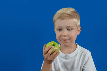 The baby is looking at a green apple. Health food