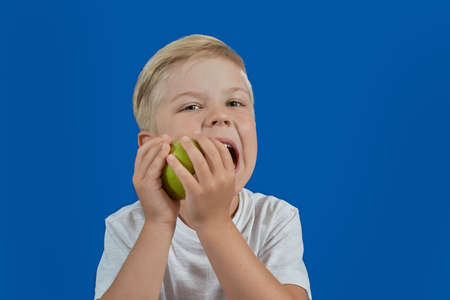 Young boy eating green apple 写真素材
