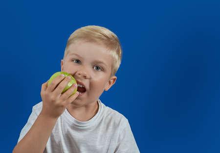 Funny child eating green apple. Health food Foto de archivo