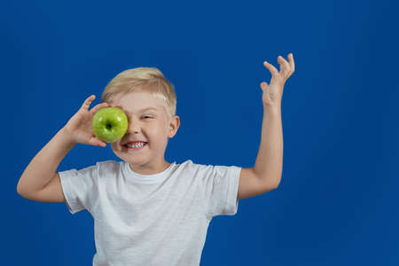 The boy holds a green apple. Health food Foto de archivo