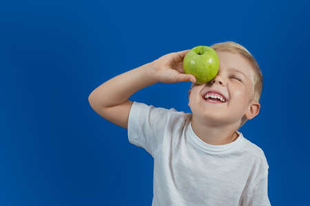Funny boy looks at the apple. Health food