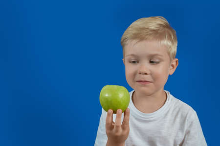 The baby is looking at a green apple