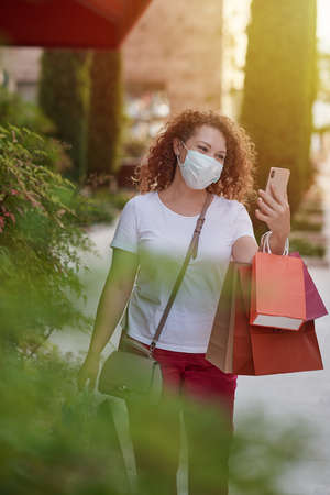 Young woman in mask out on a shopping spree