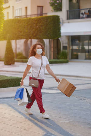 Young woman in a mask going shopping in the city