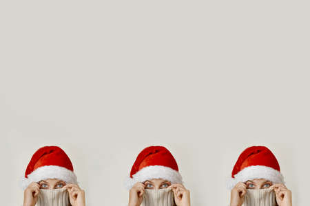 Three women heads concept in santa hat, covering his face with a collar Stock Photo