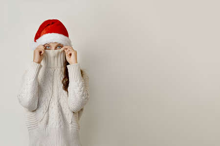 Woman in santa hat on his head, covering his face with a collar Stock Photo