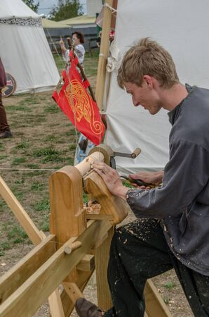 Levin, New Zealand - February 10, 2018: Medieval reenactor works on a foot-powered lathe at a medieval market in Levin showgrounds, New Zealand. 에디토리얼