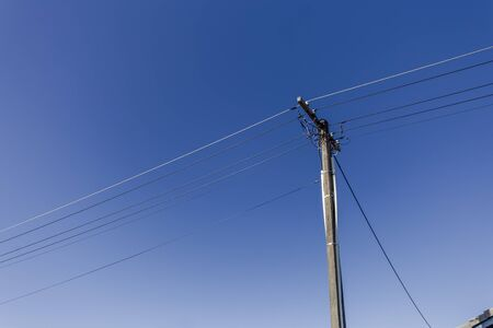 Pole with electric power lines and a blue sky Stockfoto