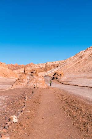 San Pedro De Atacama, Chile - September 29, 2016: Security guard on a bicycle in the Dunes of Moon Valley in Atacama Desert, Chile.