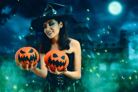 Young witch carrying two pumpkins in halloween night. Witch in haunted garden with green smoke and full moon.