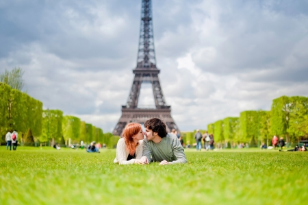 city life: Loving couple lying on the grass on the Champ de Mars in Paris with the Eiffel Tower in the Background Stock Photo
