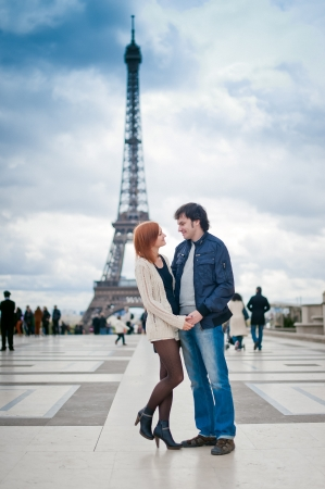 Lovers in Paris with the Eiffel Tower in the Background photo