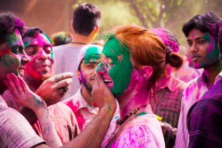 Woman tourist celebrating the Indian festival of Holi with the local Indian population  People at the holi festival in India  Holi, or Holli,is a spring festival celebrated by Hindus, Sikhs and others  The main day, Holi, is celebrated by people throwing