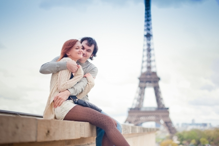 luna de miel: Los amantes abrazan en París con la Torre Eiffel en el fondo