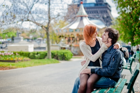 Lovers sitting on a bench in the park in Paris with the Eiffel Tower in the Background