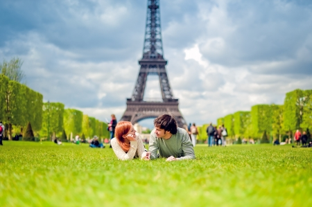 Loving couple lying on the grass on the Champ de Mars in Paris with the Eiffel Tower in the Background Stockfoto