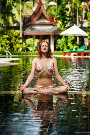 Woman doing yoga and meditating in the lotus position photo