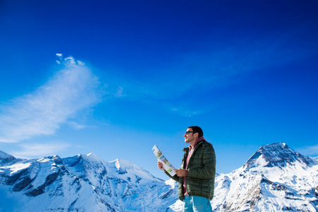 grossglockner: Man with a map looking forward to the background of snowy mountains. Grossglockner, Austria