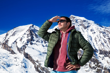Tourist on the background of snowy mountains photo