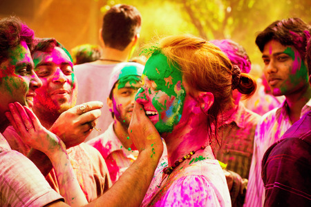 india people: Woman tourist celebrating the Indian festival of Holi with the local Indian population. People at the holi festival in India. Holi, or Holli,is a spring festival celebrated by Hindus, Sikhs and others. The main day, Holi, is celebrated by people throwing
