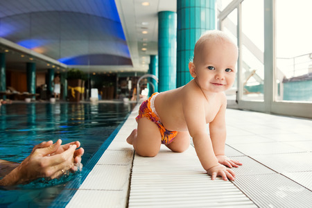 6 12 months: Portrait of a smiling charming 11 months child in the classroom in a swimming pool