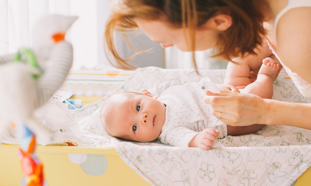 nude baby: Mother gently care of baby on the changing table at home
