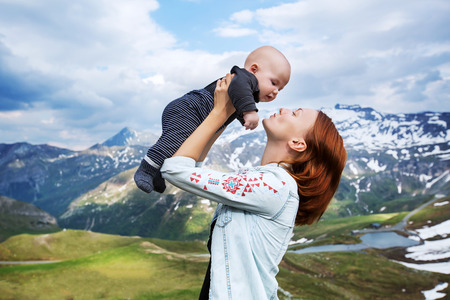 0 3 months: Baby and mother with the Alps mountains in nature in the Background