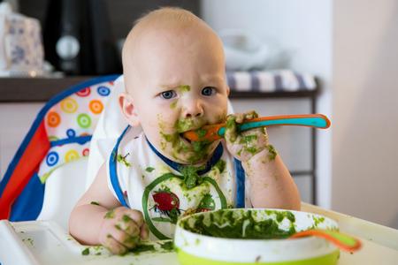 niños comiendo: Alimentación. niño del bebé adorable que come con una cuchara en una silla alta. primer alimento sólido del bebé