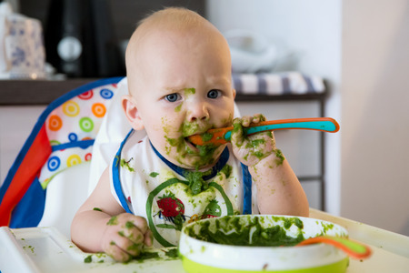 children eating: Feeding. Adorable baby child eating with a spoon in high chair. Babys first solid food
