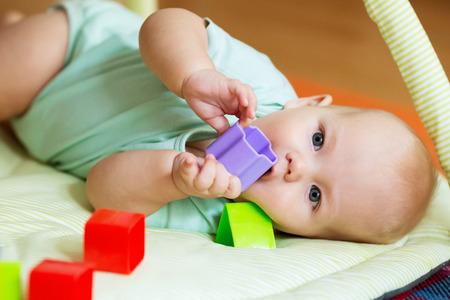 Bebé jugando con juguetes de colores Foto de archivo - 54758444