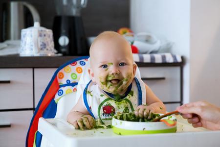 familia comiendo: Alimentación. niño del bebé adorable que come con una cuchara en una silla alta. primer alimento sólido del bebé