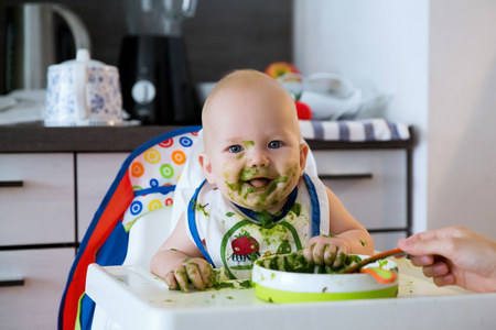 solid food: Feeding. Adorable baby child eating with a spoon in high chair. Babys first solid food